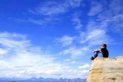 Boy on top of mountain enjoying the view (photo: DesignPics Inc.)