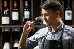 Sommelier smelling flavor of red wine in bokal on background of shelves with bottles in cellar. Male appreciating color, quality and sediments of drink. Professional degustation expert in winemaking. (photo: )